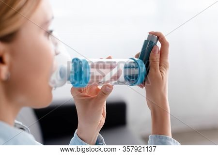 Selective Focus Of Asthmatic Woman Using Inhaler With Spacer