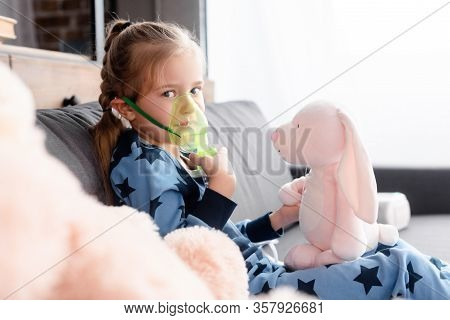 Selective Focus Of Asthmatic Kid Using Respiratory Mask Near Soft Toys