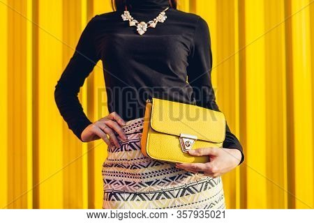 Fashion. Young Woman Holding Stylish Yellow Handbag Wearing Skirt Outdoors. Spring Female Clothes An