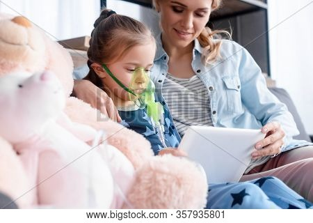 Selective Focus Of Asthmatic Kid Using Respiratory Mask And Holding Digital Tablet Near Mother And S