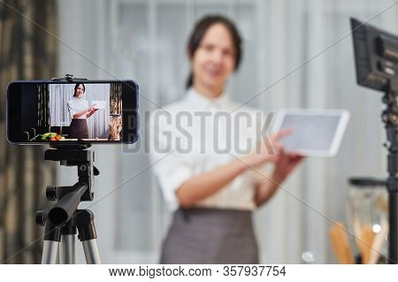 Vlogger Recording Video For Food Channel. Female Vlogging With Her Mobile Phone Mounted On A Tripod
