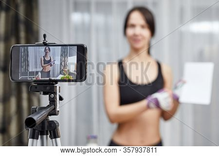 Woman Healthy Blogger Is Showing Diet Food. Vlogger Recording Vlog Video Live Streaming At Home. Fit