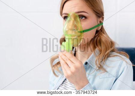Asthmatic Blond Woman Using Green Respiratory Mask