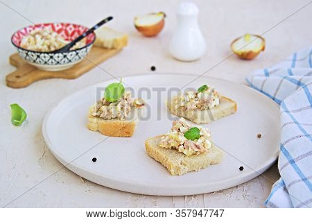 Appetizer, Salad Of Canned Cod Liver, Boiled Egg And Onion On Slices Of Fresh White Bread On A Light