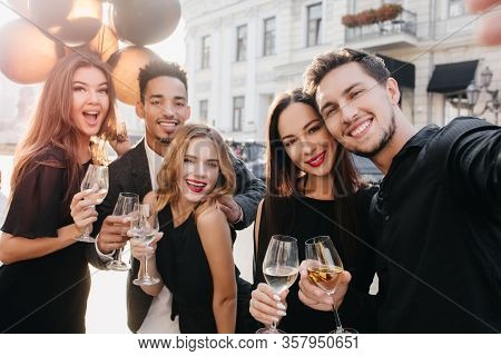 European Guy With Cute Smile Making Selfie During Street Fest In Sunny Day. Adorable Caucasian Woman