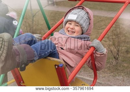A Cheerful Child Is Swinging On A Swing. Sunny Spring Day At The Playground. Girl Sitting On A Red S