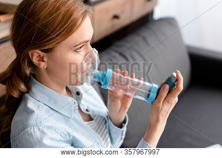 Asthmatic Woman Using Inhaler With Spacer In Living Room