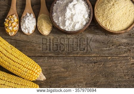 Corn Flour And Starch In Wooden Bowl And Spoon With Dried Corn Groats, Kernels On Rustic Table. Corn