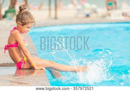 Side View Little Girls Sisters Swim In The Pool And Splashes Water On Each Other During A Vacation I