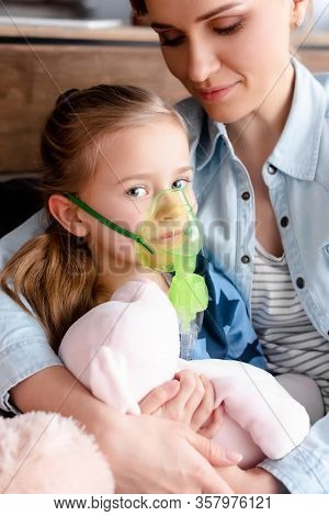Asthmatic Kid Using Respiratory Mask Near Mother