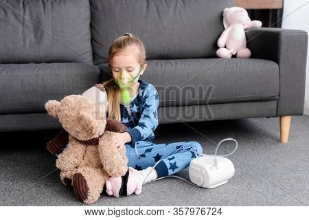 Asthmatic Child Using Compressor Inhaler And Holding Teddy Bear
