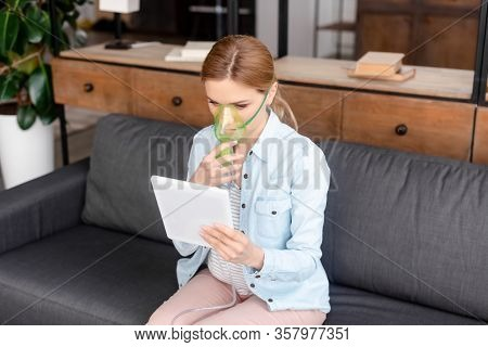Asthmatic Woman In Respiratory Mask Using Digital Tablet