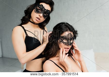 Sexy Lesbians In Black Lingerie And Lace Masks On Bed
