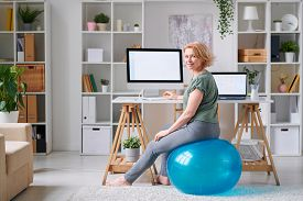 Mature sportswoman in activewear looking at you while sitting on fitball in front of computer screen and surfing for online workout