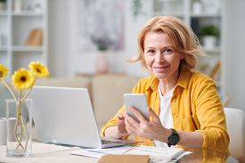 Smiling mature blond businesswoman with smartphone looking at you while working remotely in front of laptop on quarantine