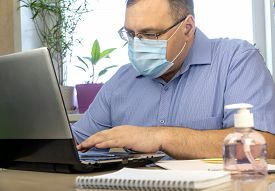 Quarantine Due To The Coronavirus Pandemic. Business Man Working From Home, Wear A Protective Mask.