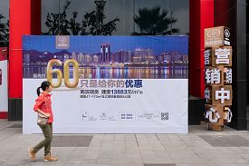 Chongqing, China - Sep 1, 2019: Property Buyer Walking Pass A Billboard Advertising New Apartment Fo