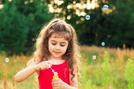 Cute Little Girl Blowing Soap Bubbles At The Field At Summer Day - Happy Childhood Concept