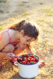 Portrait Of Cute Little Gir Playing And Eating Strawberries At Summer Day