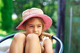 Portrait Of Cute Sad Little Girl At Big Hat  Looking Sad At Summer Day