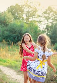 Two Happy Cute  Little Girls Having Fun And Dancing At Sunny Summer Day Outdoors