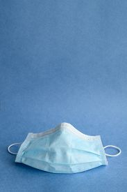 Medical Surgical Mask On A Blue Background. Face Mask To Protect The Mouth And Nose. Copy Space. Cor