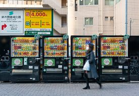 Tokyo, Japan - Mar 15, 2019: Woman Wearing Face Mask Walking Past Row Of Vending Machines In Tokyo