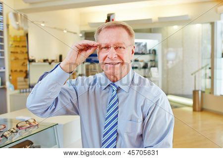 Elderly manager with new glasses at optician retail store