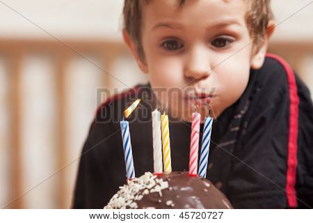 Little smiling child boy blowing birthday celebration sweet cake candle fire