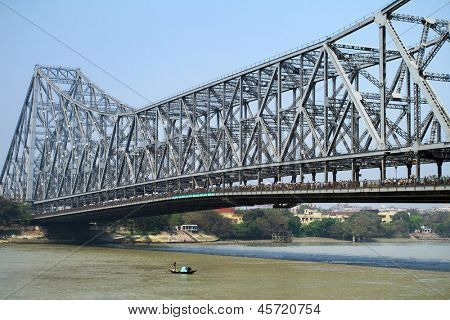 KOLKATA, INDIA - MARCH 13: Fisherman boat crosses the Hooghly River nearby the Howrah Bridge on March 13, 2013. Hooghly Bridge is a famous landmark in the city of Calcutta / Kolkata, India. poster