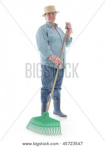 Senior woman gardener wearing straw hat and rubber boots posing with plastic lawn rake over white background