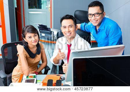Asian Creative agency - team meeting in an office with laptop