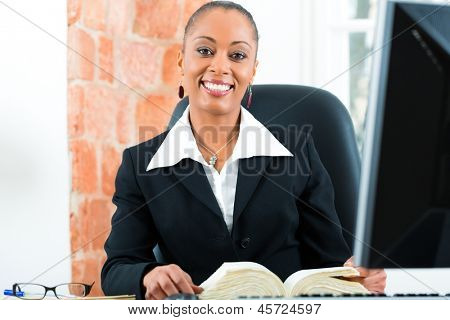 Young female black lawyer working in her office and reading a typical law book in front of a computer