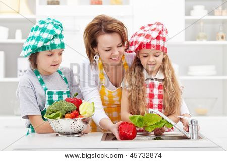 Woman and kids preparing the vegetables for a meal - washing them poster