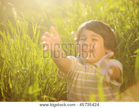 Portrait of a little boy outdoor in a summer meadow catching soap bubbles