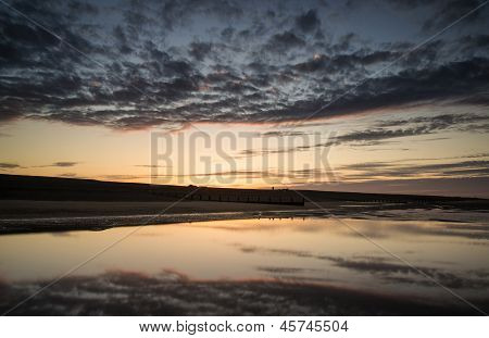Vibrant Sunrise Landscape Reflected In Low Tide Water On Beach