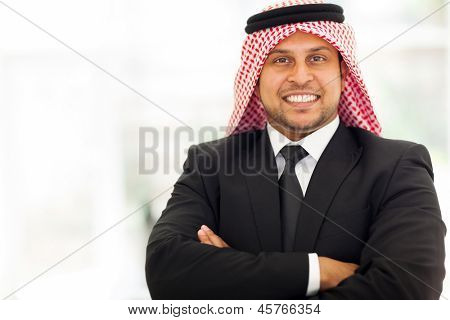 handsome arab businessman with arms crossed in office