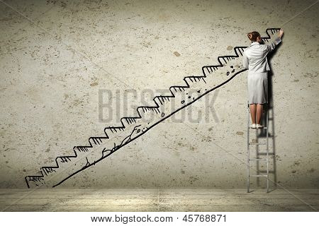 Image of businesswoman standing on ladder and drawing on wall poster