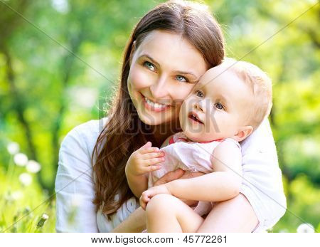 poster of Beautiful Mother And Baby outdoors. Nature. Beauty Mum and her Child playing in Park together. Outdoor Portrait of happy family. Mom and Baby portrait