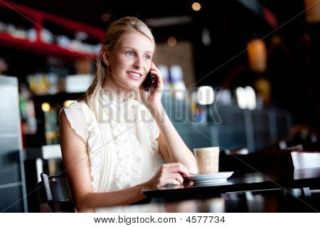 Woman On Phone In Cafe