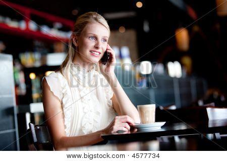 Frau am Telefon im cafe