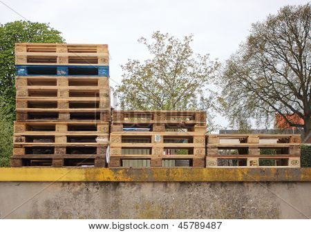 Three Piles Of Wodden Europe Pallets With One In Color