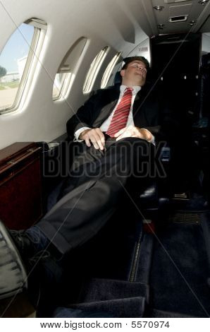 Young Businessman Sleeping In Corporate Jet