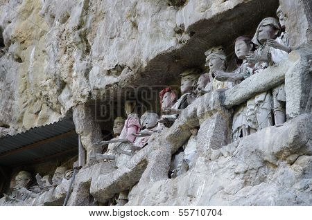 Carved figures outside of graves in a rocky cliff superstition in Toraja Sulawesi Indonesia poster