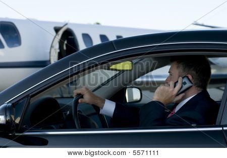 Kaufmann auf Handy in Luxus-Auto