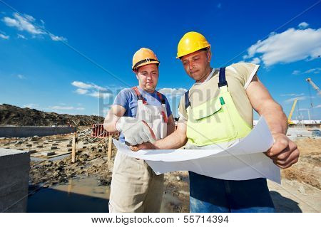 Two engineer builders with blueprint plan at construction site