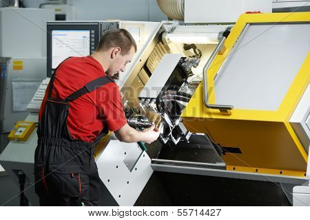 mechanical technician worker working at cnc milling machine center in tool workshop