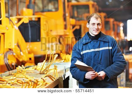 Portrait of young adult experienced industrial engineer over heavy industry machinery production line manufacturing workshop