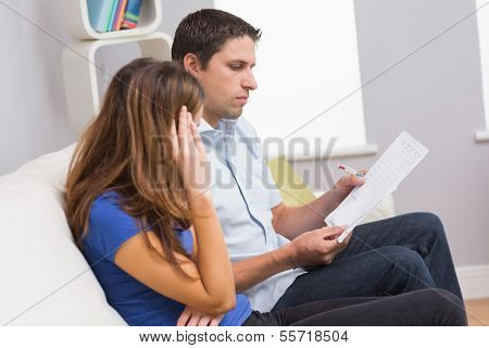 Stressed couple sitting on couch and paying their bills in the living room at home
