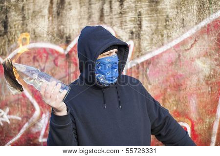 Man with Molotov cocktail on the old  wall background